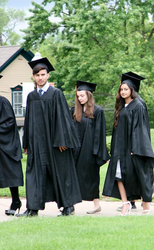 students from private high school walking outside before commencement