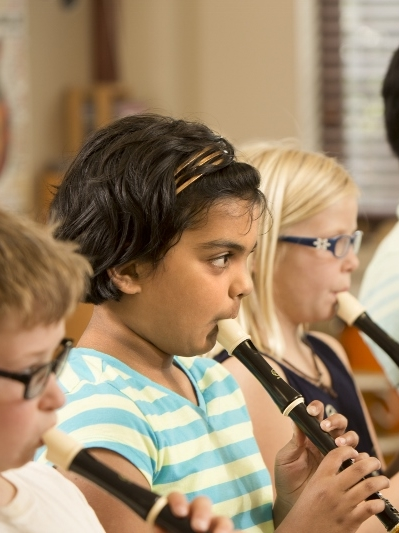 Private elementary school students playing recorders
