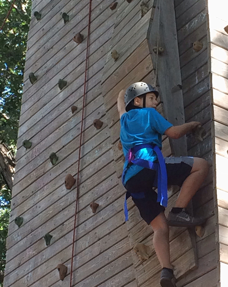 private middle school boy learning how to rock climb at field trip